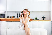 Beautiful and cute young girl in a white dress at home on the sofa cheerful and happy with headphones