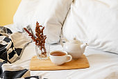 Tray of tea on bed. White bedding sheets with blanket and pillow. Breakfast in bed. Warm and cosy scandinavian hygge concept - cup of tea.