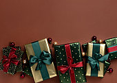 Christmas background with gift boxes, satin ribbons on brown background.