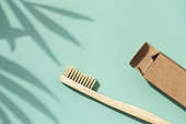 Bamboo toothbrush on mint background.