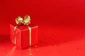 Red gift box on red background.
