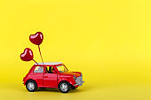 Red small toy car on vibrant background