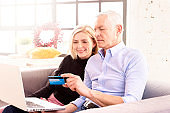 Senior couple using bank card and laptop while shopping online from home