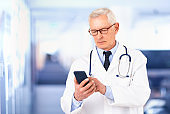 Senior male doctor text messaging on mobile phone while standing in doctor's office