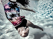 Teenage girl underwater doing ballet with light refracting off the sides of the pool.