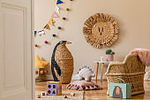 Stylish scandinavian interior of child room with natural toys, hanging decoration, design furniture, plush animals, teddy bears and accessories. Beige walls. Interior design of kid room. Template.