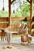 Interior design of summer gazebo by the lake with stylish rattan armchair, coffee table, sofa, pillows, plaid and elegant accessories in modern decor. Summer vibes. Chillout. Template.