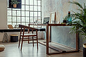 Stylish interior design of office space in loft apartment with wooden desk, chair, office supplies, laptop, plants, lamp and elegant accessories. Modern home office decor. Bright space. Template.