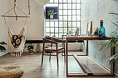 Stylish interior design of office space in loft apartment with wooden desk, chair, office supplies, laptop, plants, hammock and elegant accessories. Modern home office decor. Bright space. Template.
