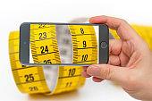Yellow measuring tape on smartphone screen.