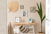 Stylish scandinavian interior of home office space with a lot of mock up photo frames, wooden desk, design chair, plants, office and personal accessories. Modern neutral home staging. Template.