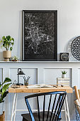 Stylish interior of home office room with black mock up poster map, wooden desk, black chair, clock, books, plants, cacti, office supplies, lamp and personal accessories in modern home decor.