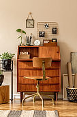 Retro interior design of art workshop room with wooden vintage bureau and chair, cube, plants, cacti, books, photos and elegant personal accessories. Stylish vintage home decor. Beige wall. Template.