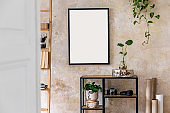 Interior design of living room with black poster mock up frame, shelf, cacti, plant, books, photo camera, wooden ladder and elegant personal accessoreis. Grunge wall. Stylish home decor. Template.
