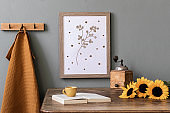 Scandinavian interior of kitchen space with wooden table, brown mock up photo frame, sunflowers, book, cup of coffee and kitchen accessories. Template, ready to use. Cozy home decor.