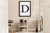 Interior design of living room with stylish furniture, ladder , tea pot, mock up poster frame, flowers and elegant accessories. Template. Modern home staging. Beige japndi concpet.