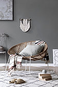 Interior design of living room at modern home with stylish rattan armchair, plaid, macrame, coffee table, books, plants and elegant accessories. Design home decor. Template. Abstract paintings