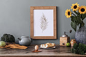 Stylish and elegant home interior of kitchen space with wooden mock up poster frame, sunflowers in vase, fresh vegetables and kitchen accessories. Nice home decor. Template. Gray color concept.