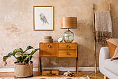 Modern retro composition of living room with wooden vintage commode, furniture, lamp, plant, carpet, pillows, gold mock up poster frame, plants, decoration and personal accessories.