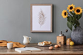 Stylish and sunny interior of kitchen space with wooden table, brown mock up photo frame, breakfast and sunflowers. Scandinavian home decor with kitchen accessories. Template. Gray color concept