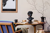 Stylish composition of elegant personal accessories at private library interior with bookstand and vintage table. Retro home decor. Candles, photo camera and a lot of books. Template. Close up.