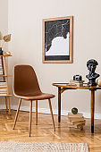 Stylish interior design of private library room with mock up poster map, brown chair, wooden table, bookstand, books and elegant personal accessories. Retro vintage home decor. Beige wall. Template.