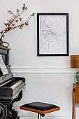 Stylish composition at living room interior with black piano, design stool, black mock up poster map, spring flowers, lamp, furniture and elegant presonal accessories in modern home decor.