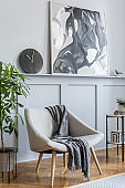 Stylish interior of living room with design grey armchair, plaid, marble stool, paintings, cacti, plants, decoration, black clock and elegant personal accessories in modern home decor.