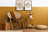 Stylish composition of living room interior with design rattan armchair, two mock up poster frames, plants, cube, palid and personal accessories in honey yellow home decor. Template.