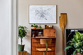 Stylish and vintage interior design of living room with wooden retro commode, plants, ships, paddle, map and elegant personal accessories. Mock up poster frame on the wall. Template. Home decor.