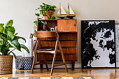 Stylish and vintage interior design of living room with wooden retro commode, chair, tropical plants, ships and elegant personal accessories. Mock up poster frame on the floor. Template. Home decor.