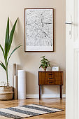Modern composition of living room interior with brown mock up poster frame, design retro commode, chair, rattan basket with palm plant and elegant accessories. Template. Stylish home staging. Japandi.