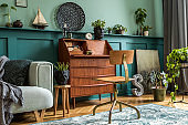 Stylish interior design with retro wooden cabinet, chair, mint sofa, plants, carpet, decoration, maps, stool and elegant personal accessories. Modern retro concept of home office space. Template.