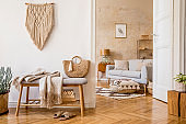Scandinavian interior of open space with wooden bench, grey sofa, pillows, palid, picture frame, macrame, plant, books, carpet, decoration and elegant personal accessoreis in stylish home decor.