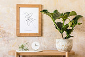 Stylish scandinavian interior of living room with mock up poster frame, wooden console, plants, clock, decoration, grunge wall and elegant personal accessories in modern home decor.