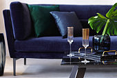 Stylish composition at living room interior with velvet sofa, pillows, coffee table, tropical leaf, wine glasses and decoration in modern concept.