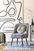 Interior design of living room with stylish gray armchair, abstract paintings on the wall, flowers in vase, pillow, plaid and elegant personal accessories. Beige concept. Modern home staging. Template