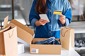 a beautiful young woman using mobile phone and credit card for online shopping with shopping bag and postal parcel box of clothing on the table