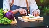 a woman cutting and chopping asparagus and carrot by knife on wooden board