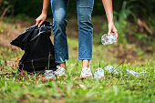a female picking up garbage plastic bottles into a plastic bag in the park for recycling concept