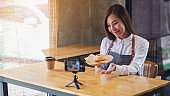 A woman food blogger or vlogger showing a piece of donut while recording a video on camera