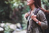A traveler with backpack walking by mountain stream for hiking concept
