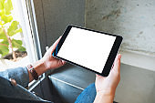 a woman holding black tablet pc with blank white screen in cafe