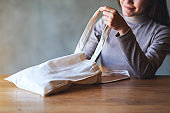 a young woman holding and looking inside a white fabric tote bag for reusable and environment concept