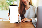 a beautiful woman holding and showing a mobile phone with blank white screen