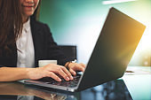 businesswoman using and typing on laptop computer keyboard while working in office