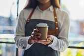 A waitress holding and serving a paper cup of hot coffee