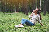 A woman enjoy listening to music with headphone with feeling happy and relaxed in the park