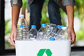 A woman collecting and holding recyclable garbage plastic bottles in a trash bin