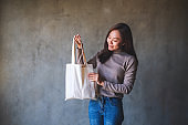 a beautiful young asian woman holding and carrying a white fabric tote bag for reusable and environment concept